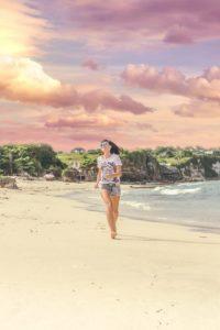 Jeune femme en short et t-shirt qui marche sur la plage